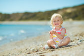 Happy baby girl playing on beach — Stock Photo