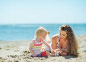 Mutter und baby mädchen spielen mit sand am strand — Stockfoto