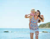 Mother and baby girl running on sea coast — Stock Photo
