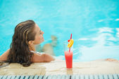 Young woman at pool with cocktail. rear view — Stock Photo