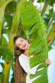 Portrait of smiling young woman among tropical palms — Stock Photo