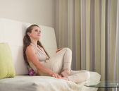 Thoughtful young woman sitting on couch — Foto de Stock