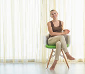 Smiling young woman sitting on modern chair — Stock Photo