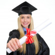 Smiling young woman in graduation gown showing diploma — Stock Photo