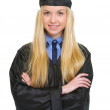 Portrait of smiling young woman in graduation gown — Stock Photo