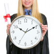 Closeup on diploma and clock in hand of woman in graduation gown — Stock Photo