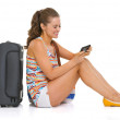 Young tourist woman with wheel bag sitting on floor and writing — Stock Photo