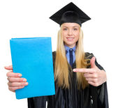 Closeup on young woman in graduation gown pointing on book — Stock Photo