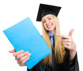 Smiling young woman in graduation gown pointing on book — Stock Photo
