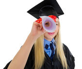 Young woman in graduation gown looking through diploma — Stock Photo