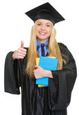 Happy young woman in graduation gown with books showing thumbs u — Stock Photo
