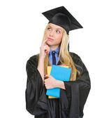 Thoughtful young woman in graduation gown with books — Stock Photo