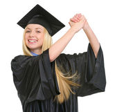 Smiling young woman in graduation gown rejoicing success — Stock Photo
