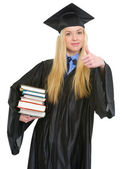 Happy young woman in graduation gown showing books and thumbs up — Stock Photo