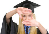 Young woman in graduation gown framing with hands — Stock Photo