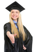 Smiling young woman in graduation gown stretching hand for hands — Stock Photo