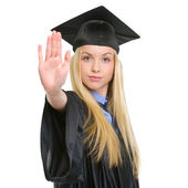 Young woman in graduation gown showing stop gesture — Stock Photo