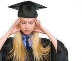 Portrait of stressed young woman in graduation gown — Stock Photo