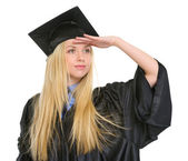 Young woman in graduation gown looking into distance — Stock Photo