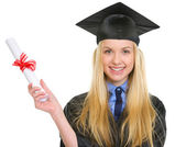 Smiling young woman in graduation gown holding diploma — Stock Photo
