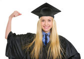 Happy young woman in graduation gown showing biceps — Stock Photo