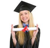 微笑显示文凭毕业长袍的年轻女人 — 图库照片
