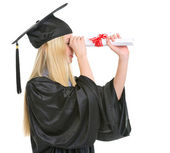 Young woman in graduation gown looking into distance through dip — Stock Photo