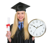 Happy young woman in graduation gown holding diploma and clock — Stock Photo