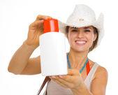 Smiling beach young woman showing sun block creme — Stock Photo