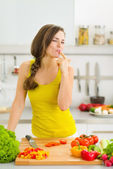 Happy young housewife tasting vegetables while cutting — Foto de Stock