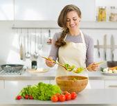 微笑着的年轻家庭主妇,混合新鲜的沙拉 — 图库照片