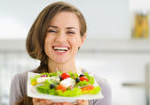 Smiling young woman showing fresh salad — Stock Photo