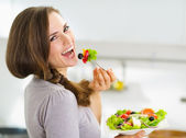 Smiling young woman eating fresh salad in modern kitchen — Photo