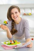 Sorrindo jovem dona de casa, comer salada fresca e lendo revista — Fotografia Stock