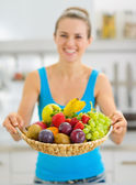 Closeup on plate of fresh fruits giving by smiling young woman — Foto Stock