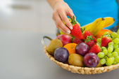 Closeup on female hand taking strawberry from plate of fresh fru — Stock Photo