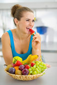 Happy young woman eating strawberry in modern kitchen — Stock Photo