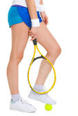 Closeup on female tennis player standing with one foot on ball — Stock Photo