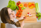 Happy young housewife cutting fresh vegetables — Stock Photo