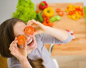 Smiling young woman holding cherry tomatos in front of face — Stock Photo