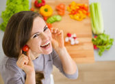 Smiling young woman using cherry tomatos as earring — Stockfoto