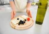 Closeup de joven ama de casa dando aceitunas y queso de corte b — Foto de Stock