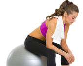 Tired fitness young woman sitting on fitness ball — Stock Photo