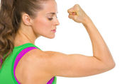 Fitness young woman showing biceps — Stockfoto