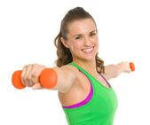 Uśmiechający się fitness młoda kobieta co ćwiczenia z hantlami — Zdjęcie stockowe
