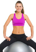 Smiling fitness young woman sitting fitness ball — Stock Photo