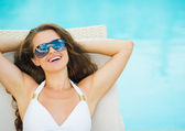 Portrait of smiling young woman laying on sunbed — Stock Photo