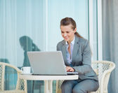 Happy business woman working with laptop on terrace — Stock Photo