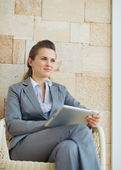 Thoughtful business woman with tablet pc sitting on terrace — Stock Photo