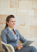 Happy business woman with tablet pc sitting on terrace — Stock Photo